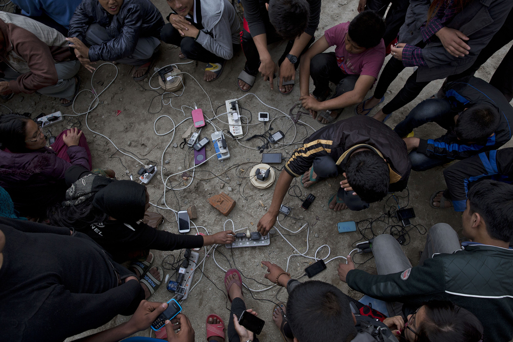 Nepalese villagers charge their cell phones in an open area in Kathmandu, Nepal, Monday, April 27, 2015. (AP Photo/Bernat Armangue)