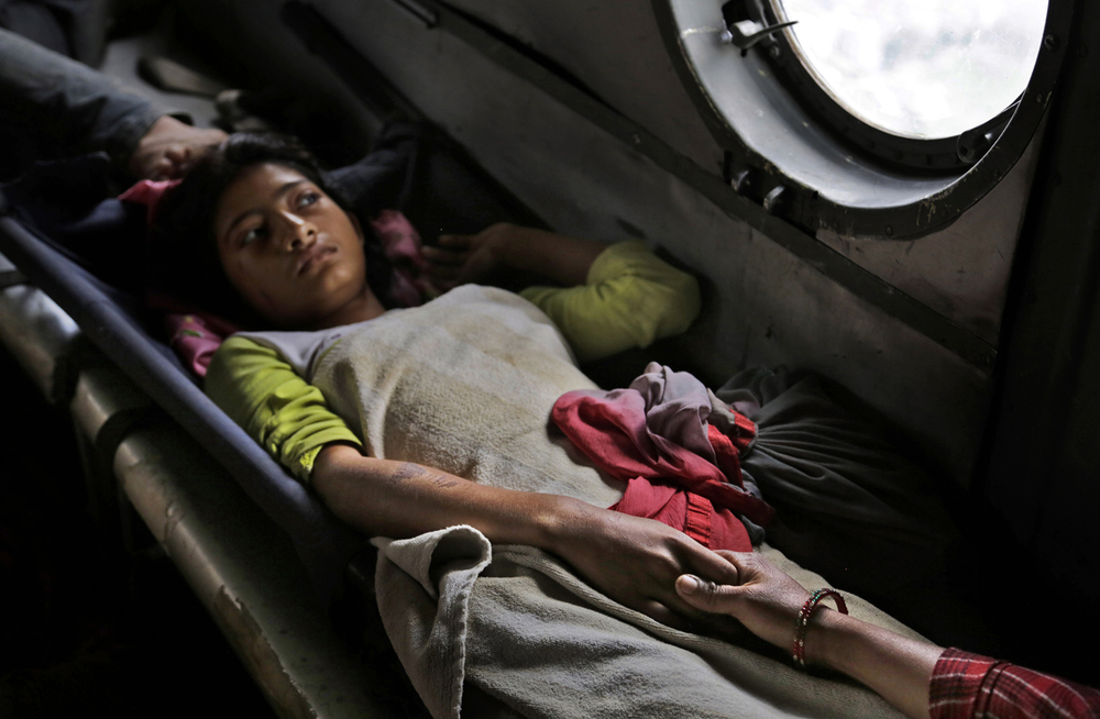 A girl injured in Saturday's earthquake holds the hand of her mother inside an Indian air force helicopter as they are evacuated from Trishuli Bazar to Kathmandu airport in Nepal, Monday, April 27, 2015. (AP Photo/Altaf Qadri)