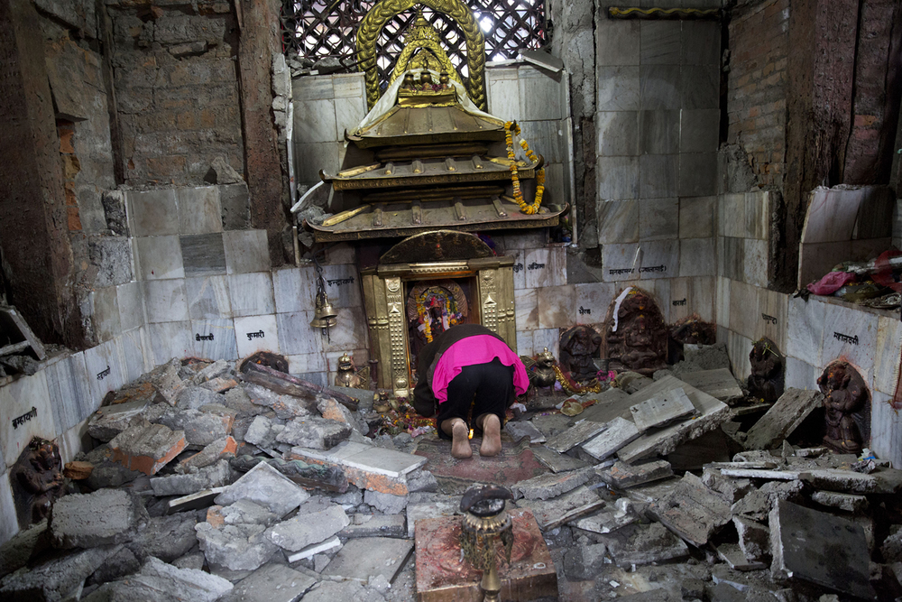 A Hindu Nepalese woman offers prayers at Indrayani temple, which was damaged in Saturday's earthquake in Kathmandu, Nepal, Monday, April 27, 2015. (AP Photo/Bernat Armangue)