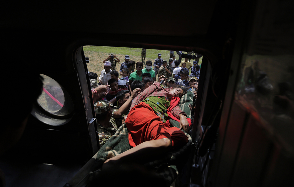 An injured woman is carried to an Indian air force helicopter as they evacuate victims of Saturday's earthquake from Trishuli Bazar to Kathmandu airport in Nepal, Monday, April 27, 2015. (AP Photo/Altaf Qadri)