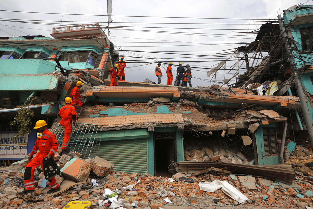 India's National Disaster Response Force personnel look for survivors in a building, in Kathmandu, Nepal, Sunday, April 26, 2015. (AP Photo/Manish Swarup)