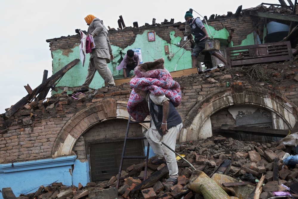 Residents rescue items from the remains of a house that was damaged in Saturday's earthquake in Kathmandu, Nepal, Monday, April 27, 2015. (AP Photo/Bernat Armangue)