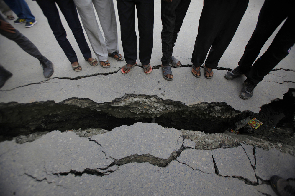 Evidence of the 7.8 magnitude earthquake is evident in the roadway in Kathmandu, Nepal, Sunday, April 26, 2015. (AP Photo/Niranjan Shrestha)