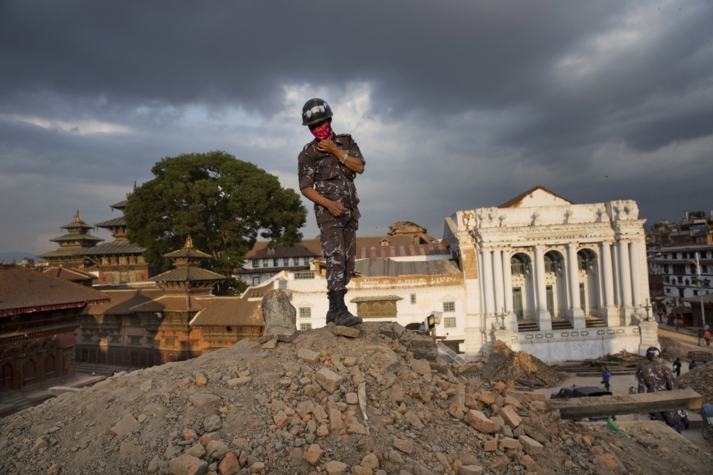 A Nepalese policeman stands atop a pile of rubble at Basantapur Durbar Square after it was damaged in Saturday's earthquake in Kathmandu, Nepal, Sunday, April 26, 2015. (AP Photo/Bernat Armangue)