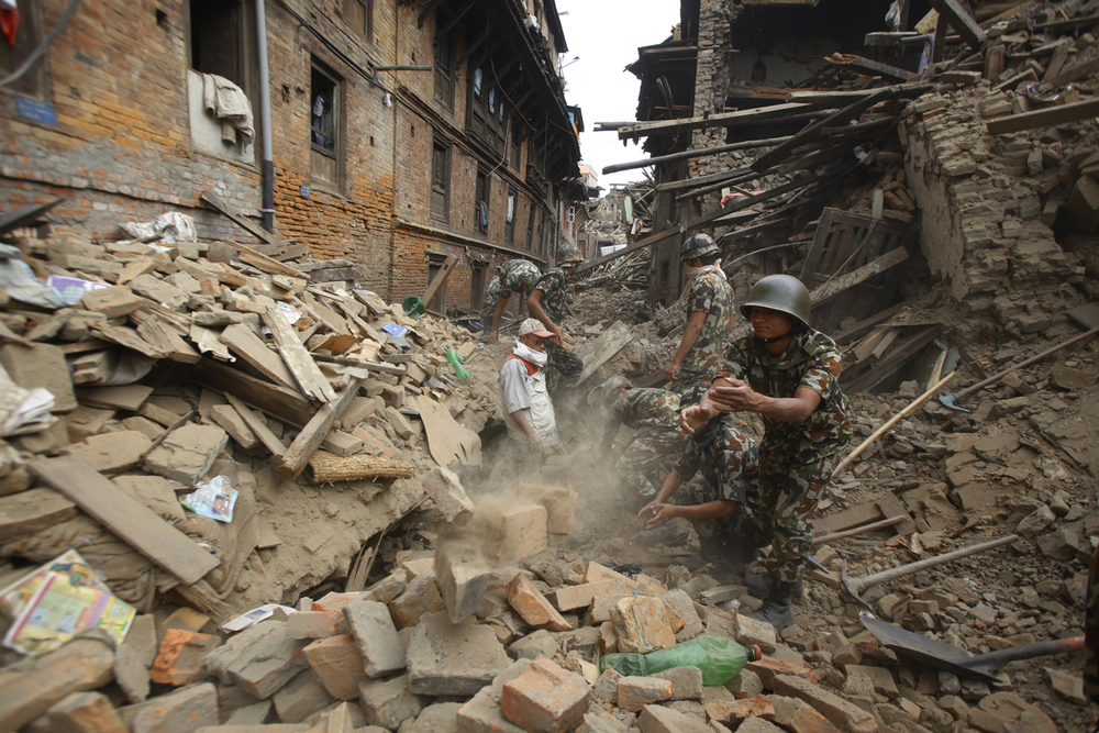 Rescue workers remove debris as they search for victims of the earthquake in Bhaktapur near Kathmandu, Nepal, Sunday, April 26, 2015. (AP Photo/Niranjan Shrestha)