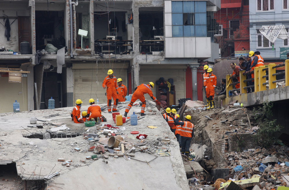 India's National Disaster Response Force (NDRF) personnel look for survivors in the debris of Saturday's earthquake, in Kathmandu, Nepal, Sunday, April 26, 2015. (AP Photo/Bikram Rai)