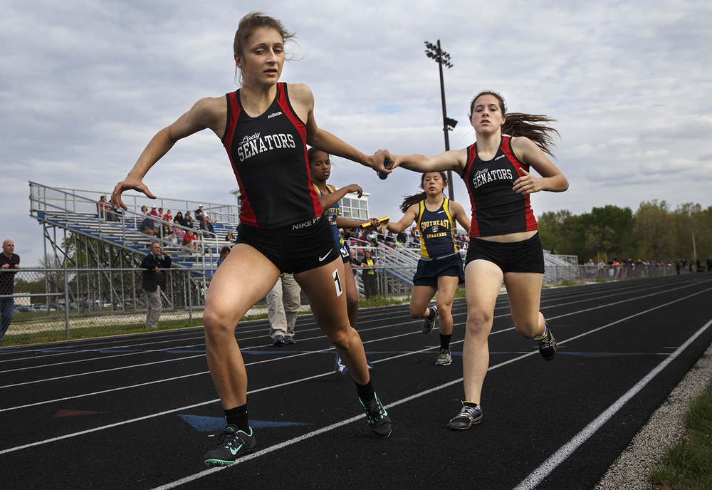 Springfield's Katy Canum hands the baton to Carrie Rolf during the 4x800 meter run during the 2015 Class AA Girls City meet at Southeast High School Wednesday, April 29, 2015. Ted Schurter/The State Journal-Register