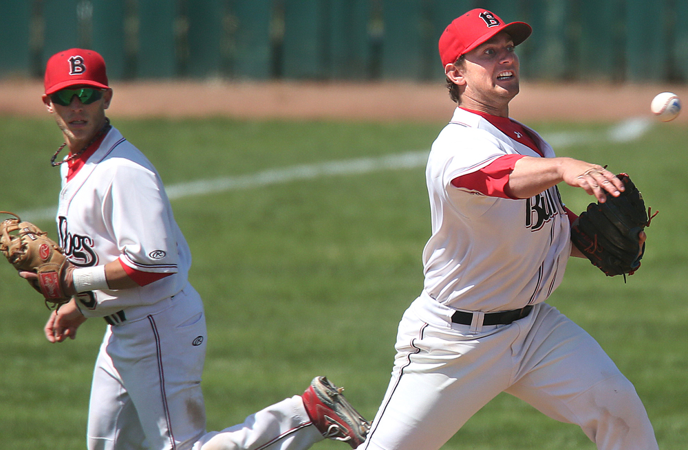 In fourth inning action in which the Spartans scored their first run, Bulldogs infielder Blake Gand attempts to get a runner out at first after a slight bobble while teammate Blake Gand looks on at left. David Spencer/The State Journal-Register