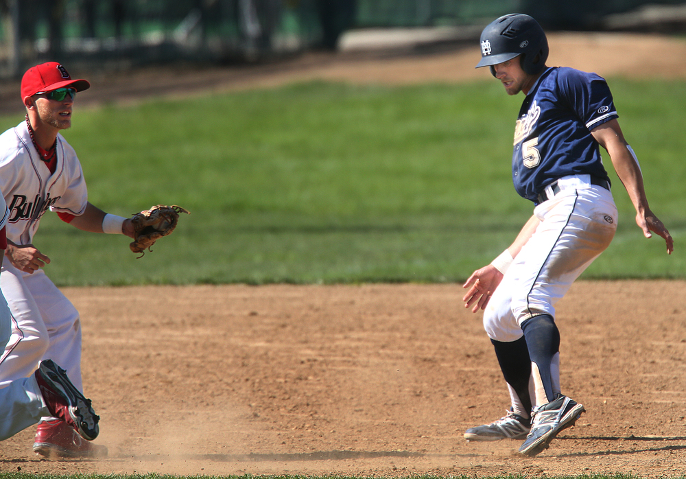 In seventh inning action, Spartans baserunner Jeff Smith is tagged out in a pickle by Bulldogs infielder Chris Day at left. David Spencer/The State Journal-Register