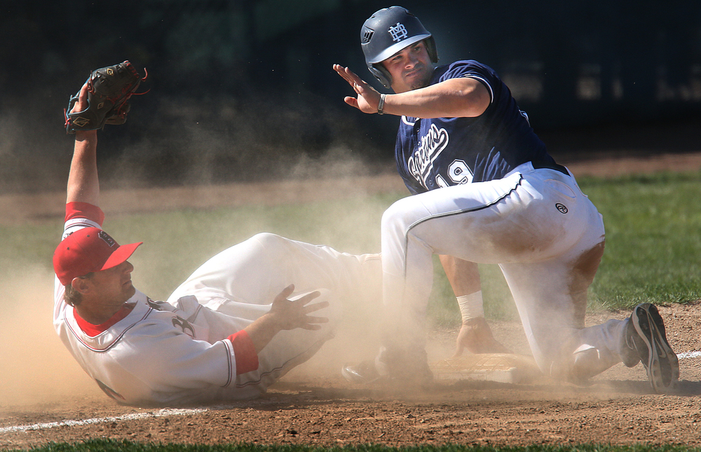 Spartans baserunner Orlando Olivera is safe at third in seventh inning action. Bulldogs third baseman Blake Gand is at left. David Spencer/The State Journal-Register