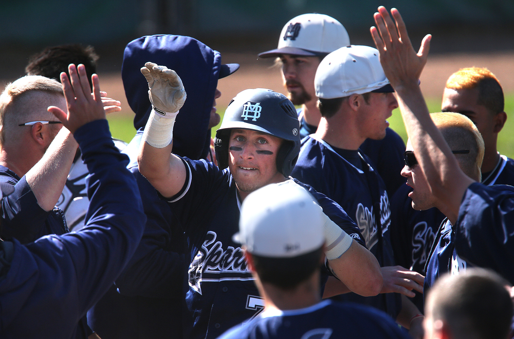 Spartans baserunner Brent Zimmerman is welcomed home by teammates after scoring his team's second run of the game in the seventh inning. David Spencer/The State Journal-Register
