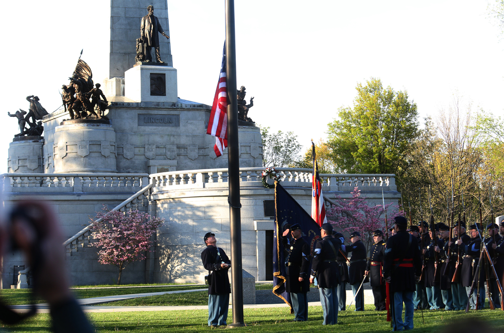 The flag is lowered in front of the tomb. A flag retreat ceremony was presented by the 114th Regiment Illinois Volunteer Infantry (Reactivated) at the Lincoln Tomb in Springfield's Oak Ridge Cemetery on Friday evening, May 1, 2015. An extra large crowd by those from around the country visiting Springfield for the 150th Lincoln Funeral Weekend had perfect weather for the ceremony. David Spencer/The State Journal-Register