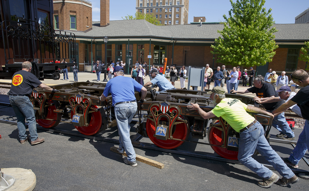 Volunteers with the Lincoln Funeral Train Coalition push the wheel sets under the funeral car at the Amtrak Station Friday, May 1, 2015. The car was set up after arriving in Springfield on a trailer and will be part of the funeral re-enactment Saturday. Rich Saal/The State Journal-Register