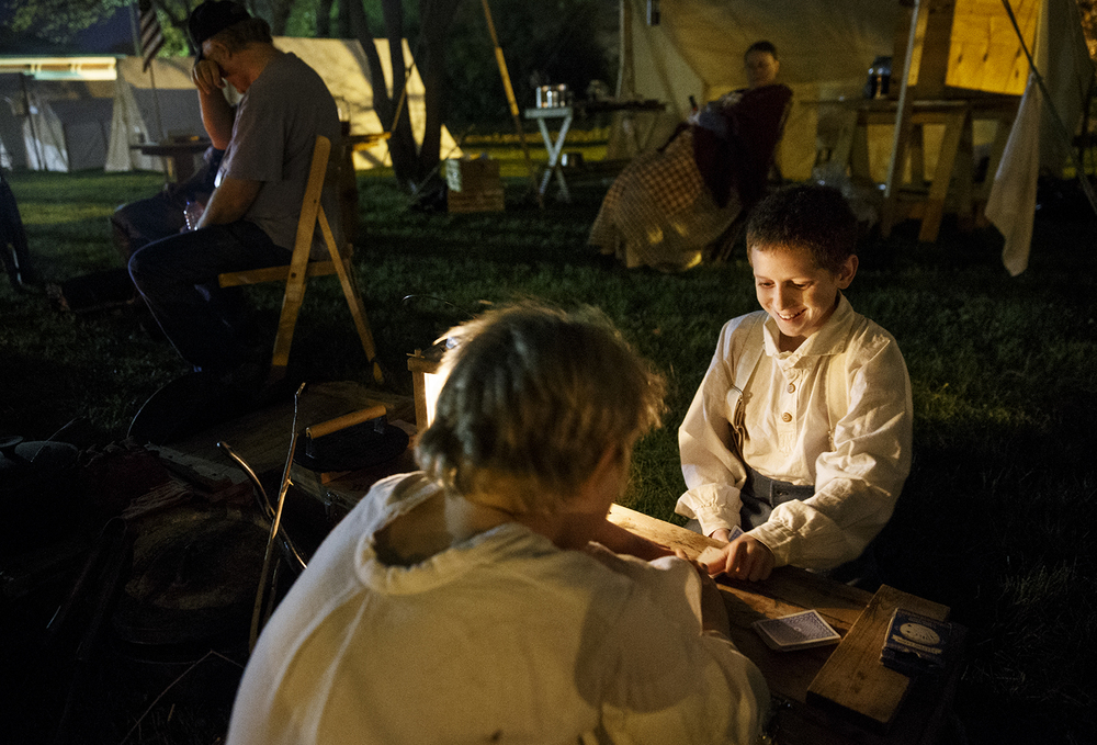 Tony Winters, left, and Draven Kyger play a game of war by lantern light at the the 10th Illinois Volunteer Cavalry Regiment Reactivated encampment on the grounds of the Springfield Art Association Friday, May 1, 2015. Members of the regiment began camping on the grounds Thursday night in preparation for the 150th anniversary of Abraham Lincoln's funeral weekend. Ted Schurter/The State Journal-Register