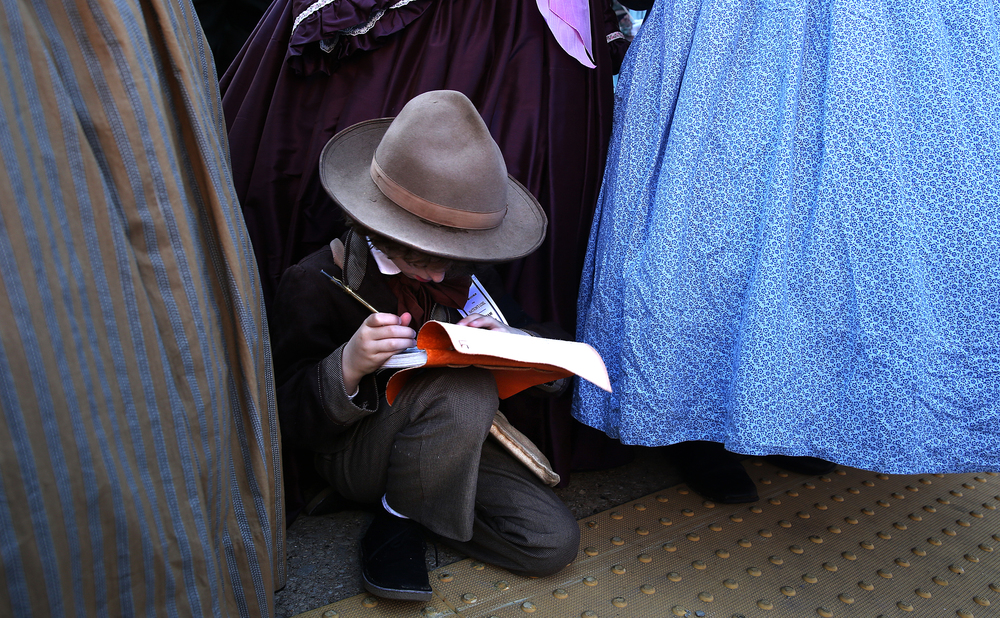 Hundreds of re-enactors in period clothing stood and waited for the funeral procession to begin outside the train station, including Josiah Reinholz of Burlington, Wis., who spent the time sketching the train car. David Spencer/The State Journal-Register