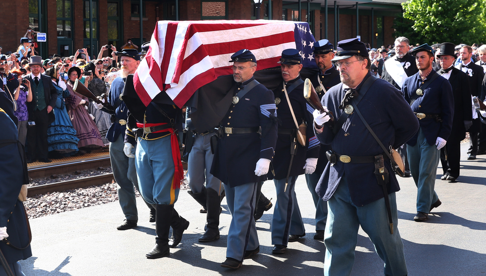 Members of the 114th Illinois Volunteer Infantry, Re-activated, carry the flag-draped Lincoln coffin past spectators to the waiting hearse. David Spencer/The State Journal-Register