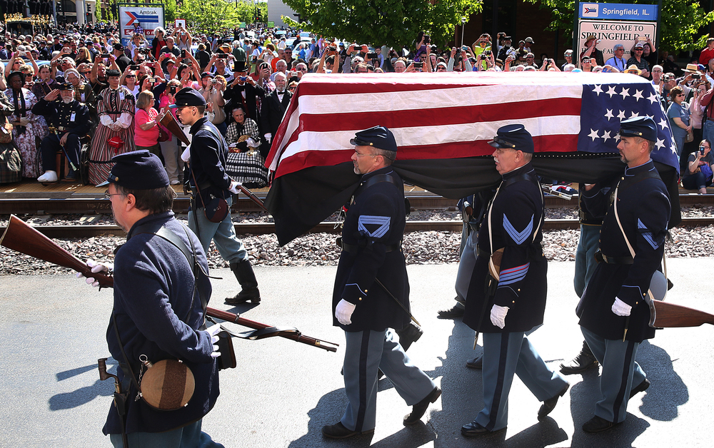Members of the 114th Illinois Volunteer Infantry, Re-activated, carry the flag-draped Lincoln coffin past spectators in route to the waiting hearse at the train station Saturday morning. David Spencer/The State Journal-Register