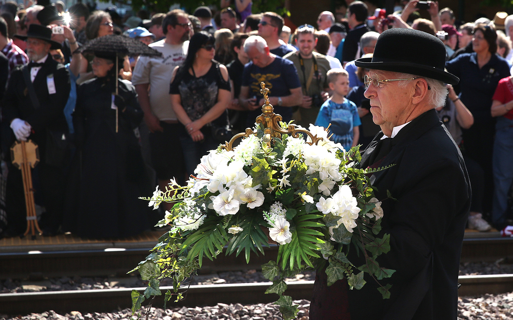 A floral bouquet adorned with a Cross is carried separately behind the coffin during the procession outside the train station. David Spencer/The State Journal-Register