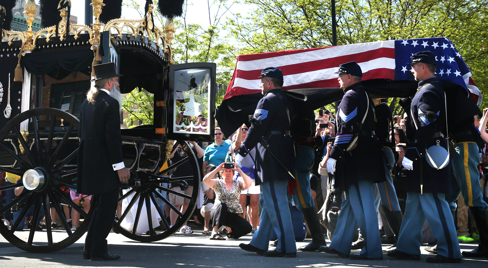 Members of the 114th Illinois Volunteer Infantry, Re-activated, place the coffin into the hearse on Jefferson Street. David Spencer/The State Journal-Register