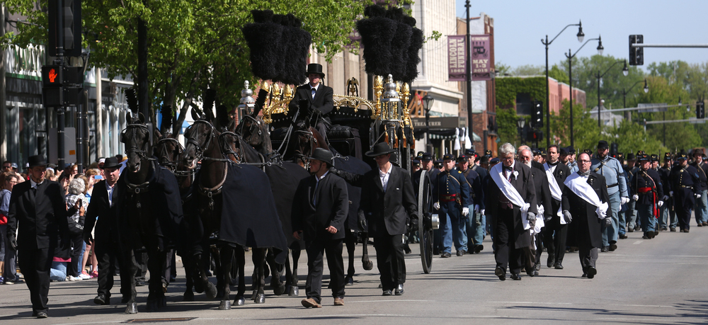 Honorary pallbearers at right, with some descended from those who originally took part in Lincoln's 1865 funeral, walk alongside the horse-drawn hearse along Fifth St. in downtown Springfield Saturday morning. David Spencer/The State Journal-Register