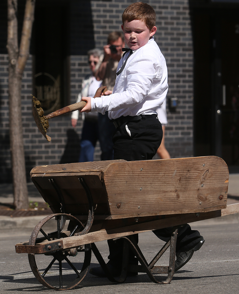 One of the most important jobs during the funeral procession was capably done by this young boy shoveling manure left by the horses on the pavement during the parade into his trusty wooden wheelbarrow. The casket of Lincoln was removed from the hearse and placed on a temporary bier in front of a large stage outside the Old State Capitol in downtown Springfield.  David Spencer/The State Journal-Register