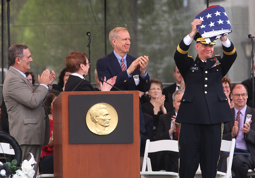 Maj. Gen. Daniel Krumrei, adjutant general of the Illinois National Guard who spoke during the funeral ceremony, holds up the replica 36-star U.S. flag that had draped the coffin during the procession. Gov. Bruce Rauner, center, presented the flag to Krumrei. Bob Caggiano, left, is vice president of sales for Annin Flagmakers and Katie Spindell was master of ceremonies. David Spencer/The State Journal-Register