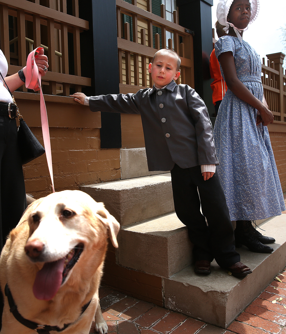 Representing Abraham Lincoln's dog Fido during the funeral procession is Roxie, a yellow Lab, who waits near the front steps of the Lincoln Home Sunday. Quinn Roderick, 6, representing the historical figure John Roll, looks on at center while Susannah Roderick, 12, representing a free African-American neighbor of the Lincoln's, Nancy Jenkins, looks on at background. David Spencer/The State Journal-Register