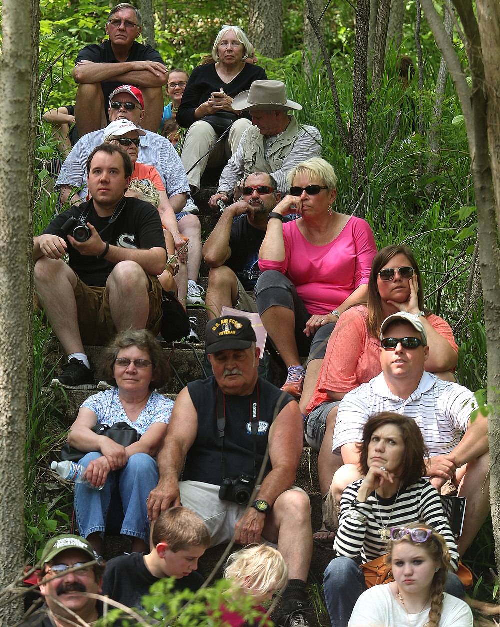 Spectators found shade while seated on steps in a wooded area close to where the ceremony was taking place across from the old Lincoln receiving vault on the grounds of Oak Ridge Cemetery Sunday afternoon. David Spencer/The State Journal-Register