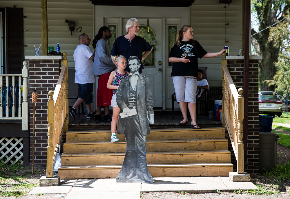 A cardboard cutout of Abraham Lincoln belonging to Ashley Seward, right, stands in front of a home on Fourth Street on the route of the funeral procession during the 2015 Lincoln Funeral Re-enactment, Sunday, May 3, 2015, in Springfield, Ill. Justin L. Fowler/The State Journal-Register