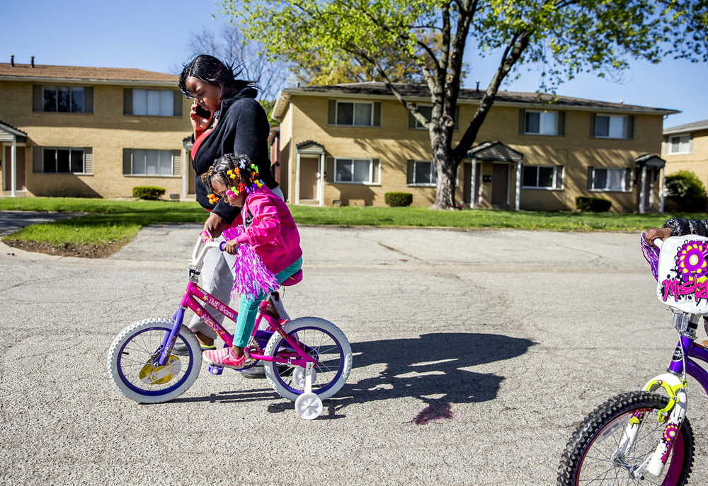 "Ziarra Smith helps her daughter, Mikashaja Poole, 4, while learning how to ride a bike with her twin sister Mikahmara Poole, 4, right, at the MacArthur Park Apartments, Monday, April 27, 2015, in Springfield, Ill. Smith has lived in the apartment complex for three years with her three daughters and has seen conditions improve. ""I can leave now and leave my door unlocked, before I couldn't do that,"" said Smith. ""It's a lot better out here."" Justin L. Fowler/The State Journal-Register"
