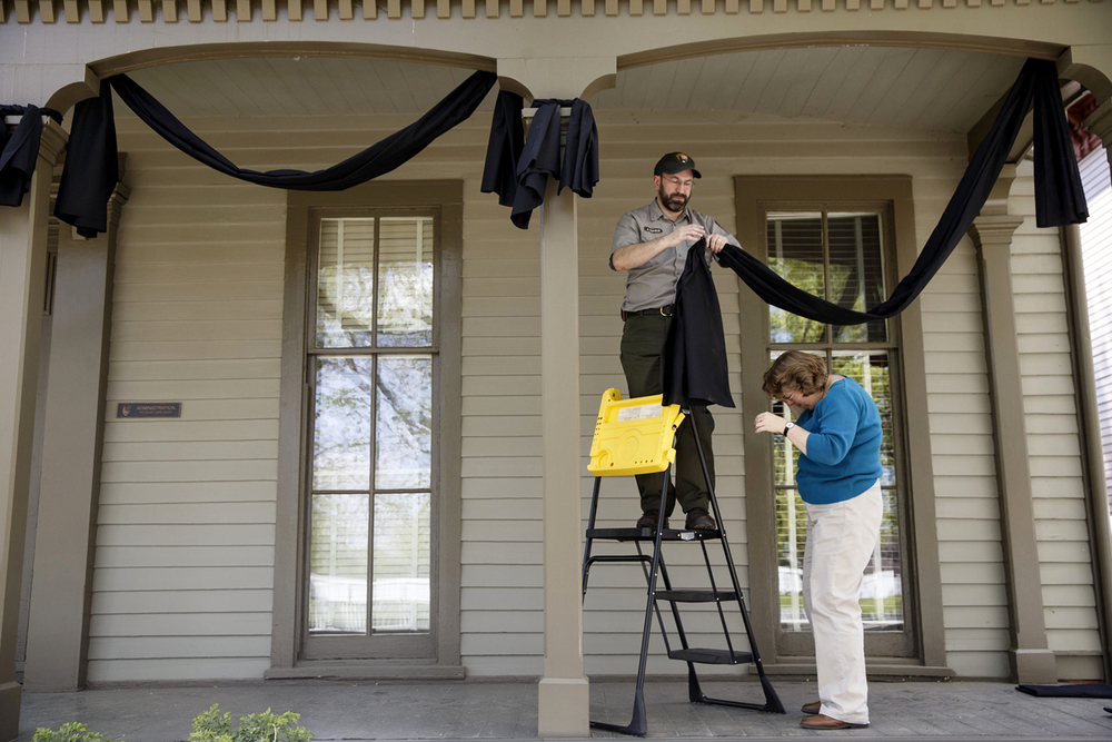 Lincoln Home National Historic Site Park Ranger John Popolis and curator Susan Haake hang black bunting on the Henson Lyon House in preparation for the 150th anniversary of Abraham Lincoln's funeral this weekend. Ted Schurter/The State Journal-Register