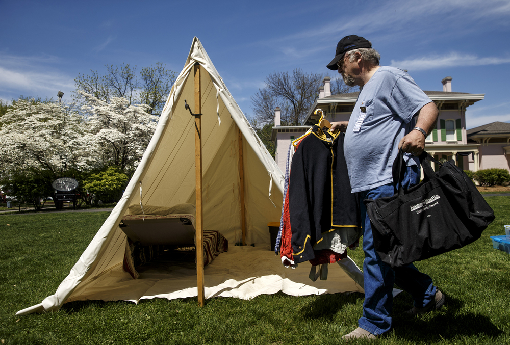 Dan Wagner of Peoria, Ill. moves luggage into his a-frame tent at the encampment for the 10th Illinois Volunteer Cavalry Regiment Reactivated on the grounds of the Springfield Art Association Friday, May 1, 2015. Some members of the regiment began camping on the grounds Thursday night in preparation for the 150th anniversary of Abraham Lincoln's funeral this weekend. Ted Schurter/The State Journal-Register