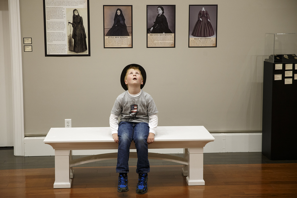 Eight-year-old Garrett Dennis of Kentucky sports a Lincoln top hat as he looks around at an exhibit of Victorian mourning customs at the Springfield Art Association Thursday, May 1, 2015. Dennis and his family were in town from northern Kentucky for the 150th anniversary of Abraham Lincoln's funeral. Ted Schurter/The State Journal-Register