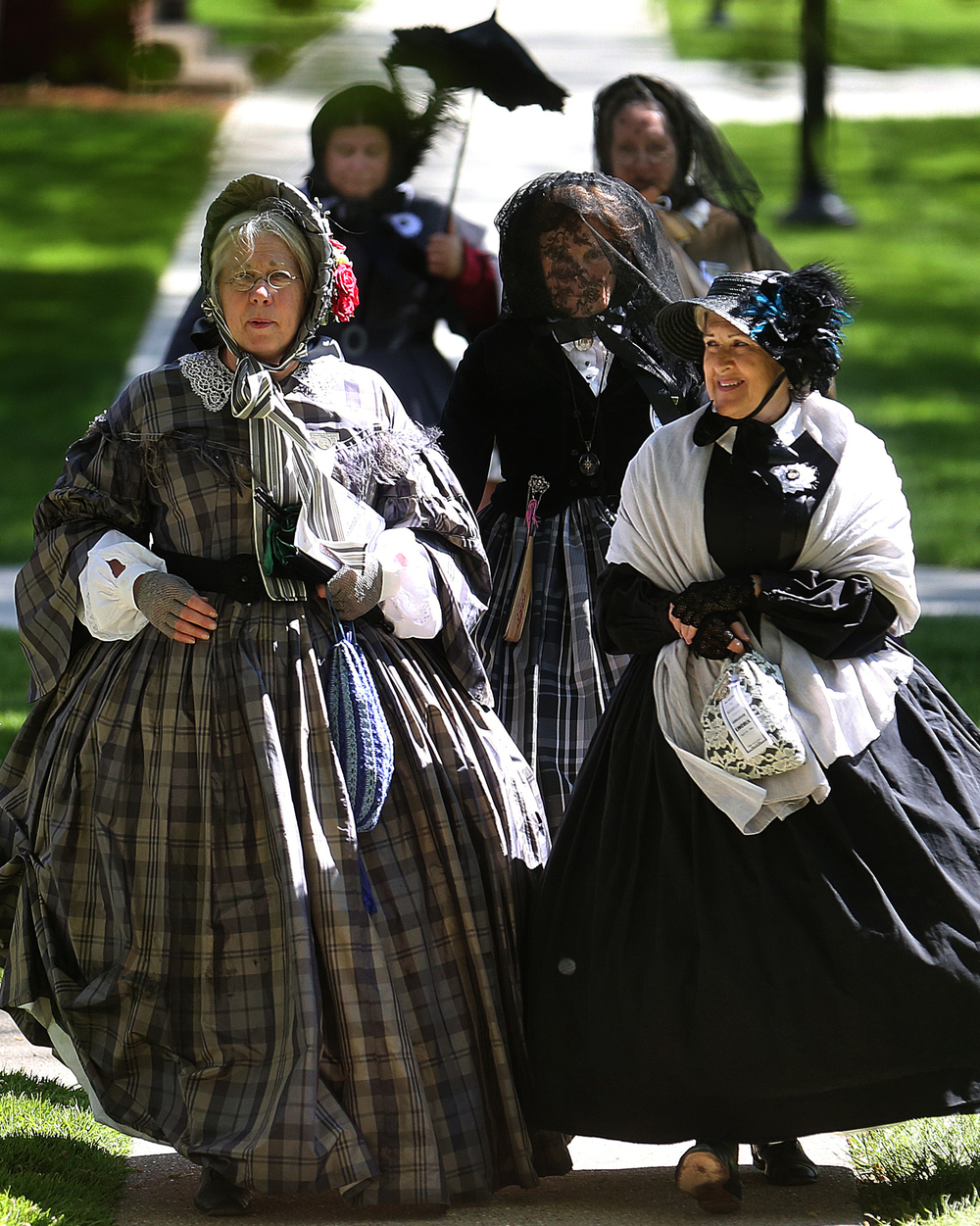 Members of the St. Louis, Mo. chapter of the Ladies Union Aid Society walk together to the Brinkerhoff Mansion and the presentation on Civil War era textiles Friday May 1, 2015.The presentation was part of the Lincoln funeral re-enactment events. David Spencer/The State Journal-Register