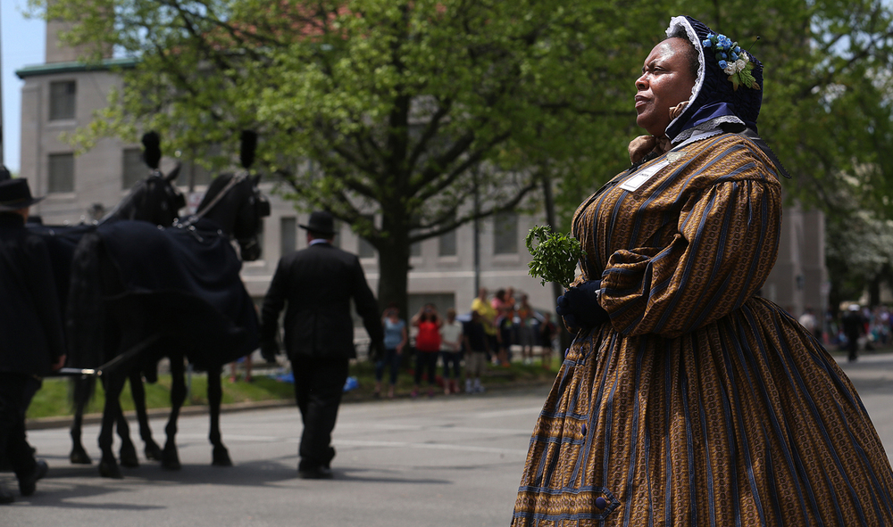 Reenactor Yulanda Burgess of Detroit, Mich., watches as the Lincoln hearse travels west on Cook Street. Burgess said her great-great grandfather, Armstead Burgess, was a member of the 6th Regiment, United States Colored Heavy Artillery who took part in the Battle of Fort Pillow. David Spencer/The State Journal-Register