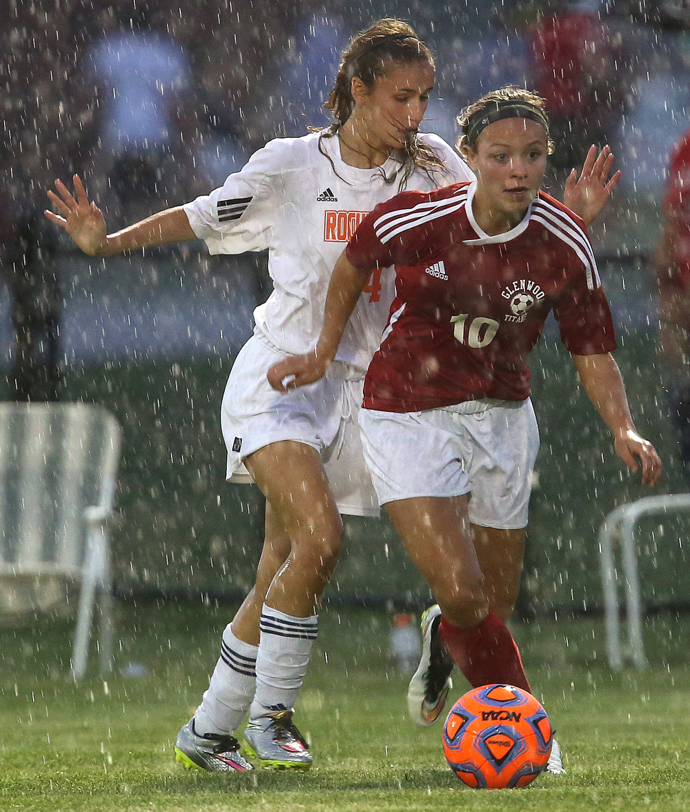 Play continued through heavy rain until lighting struck nearby forcing game suspension.  Glenwood's Kelly Graves looks to pass while Rochester defender Riley Ross comes up from behind. With neither team scoring, a weather delay with 8:45 remaining in the game forced the suspension of play between Rochester and Chatham Glenwood in girls high school soccer action at Rochester Elementary School on Thursday evening, May 7, 2015. David Spencer/The State Journal-Register