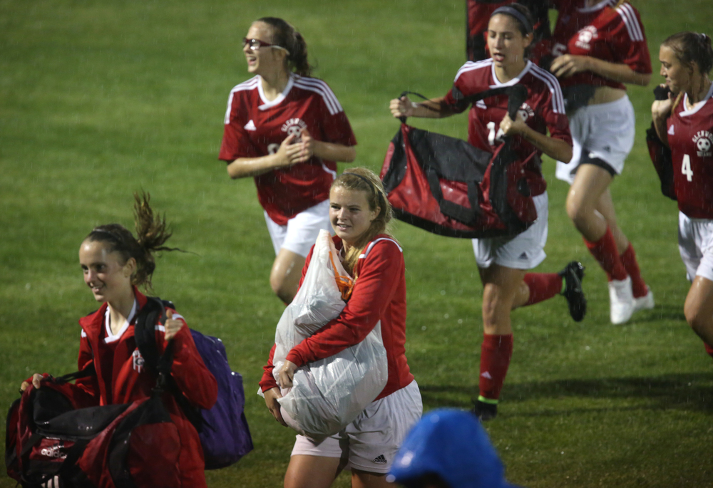 Glenwood players with equipment in tow make a run for dry cover after the game was called due to the weather. With neither team scoring, a weather delay with 8:45 remaining in the game forced the suspension of play between Rochester and Chatham Glenwood in girls high school soccer action at Rochester Elementary School on Thursday evening, May 7, 2015. David Spencer/The State Journal-Register