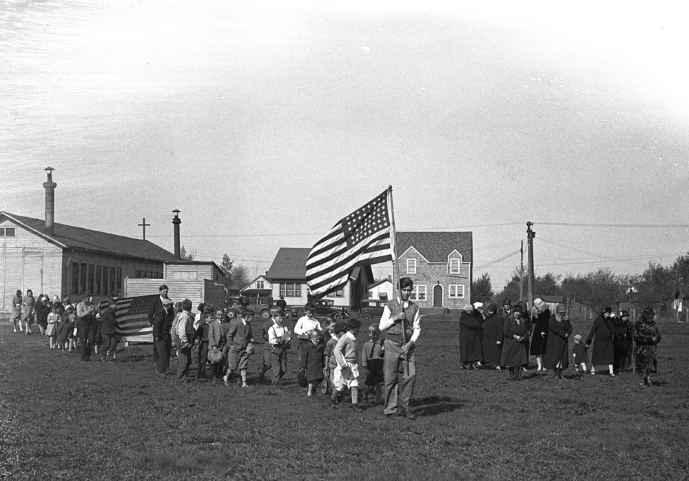 St.Aloyisus, temporary church? Students process through open field with flag. Illinois State Journal/Register glass plate negative/Sangamon Valley Collection at Lincoln Library  C-98-262  negative #1018   VF 2000-63  Pub. ISJ April 27, 1931, p.9