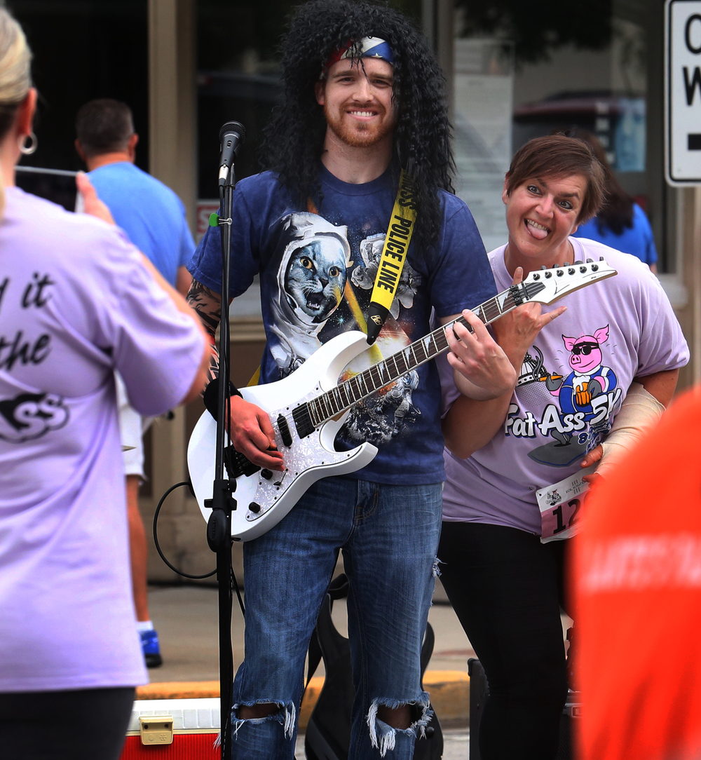 Race participant Tammy Hill of Jacksonville sticks her tongue out while being photographed alongside guitarist Cameron French who was playing with a band set up along the race route at Fourth and Monroe Streets Saturday morning. David Spencer/The State Journal-Register
