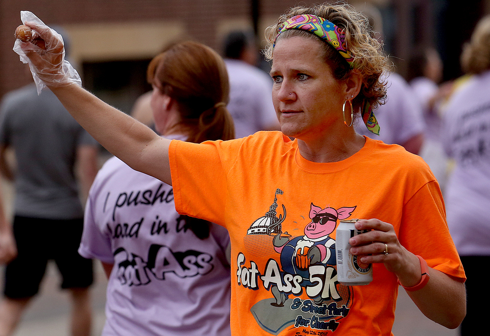 Race volunteer Carrie Tisckos was handing out donut holes to participants along Capitol Avenue. David Spencer/The State Journal-Register
