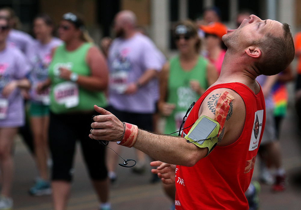 A race participant attempts to catch a thrown donut hole along Capitol Avenue. David Spencer/The State Journal-Register