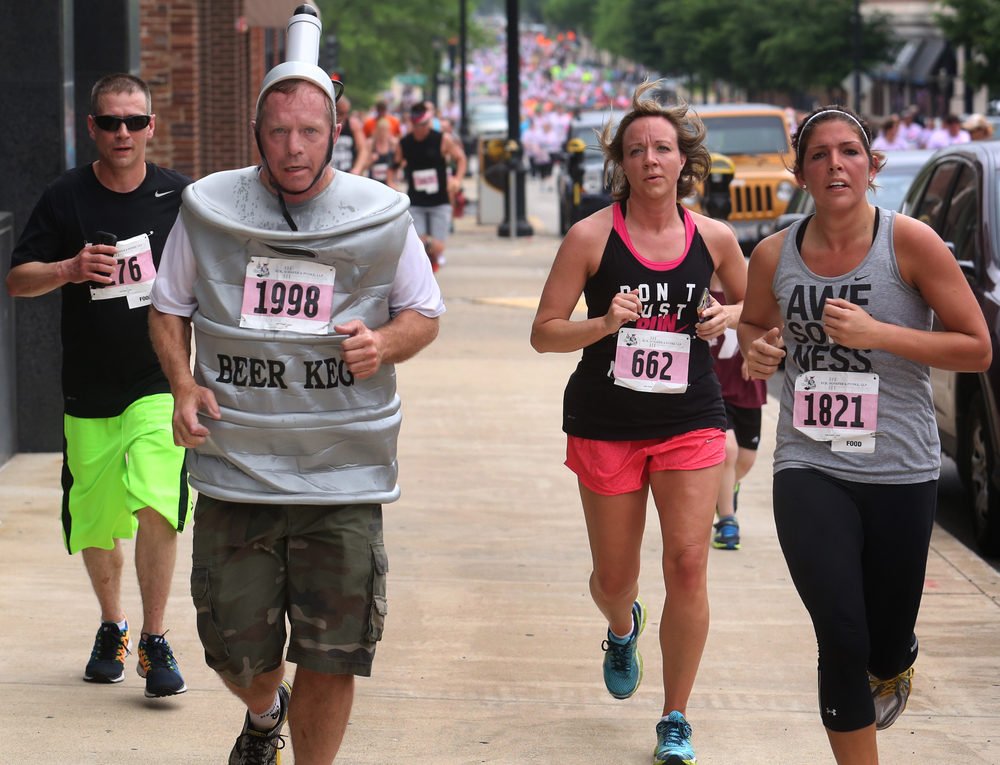 Runners, including one dressed as a keg of beer, took to the sidewalk along Fourth St. during the race. David Spencer/The State Journal-Register