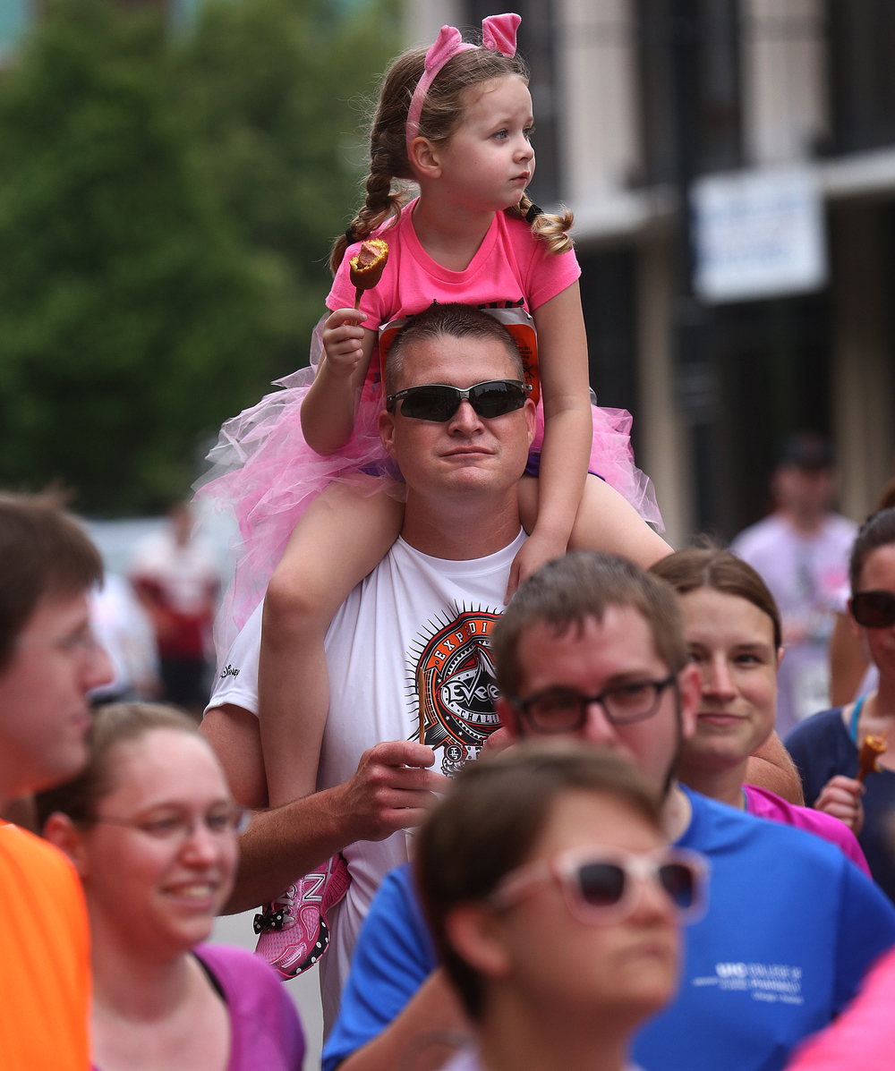 One young participant munched on a corndog while dad stood in line for some cold liquid refreshment along with others at the Craft Beer Bar race station downtown. David Spencer/The State Journal-Register