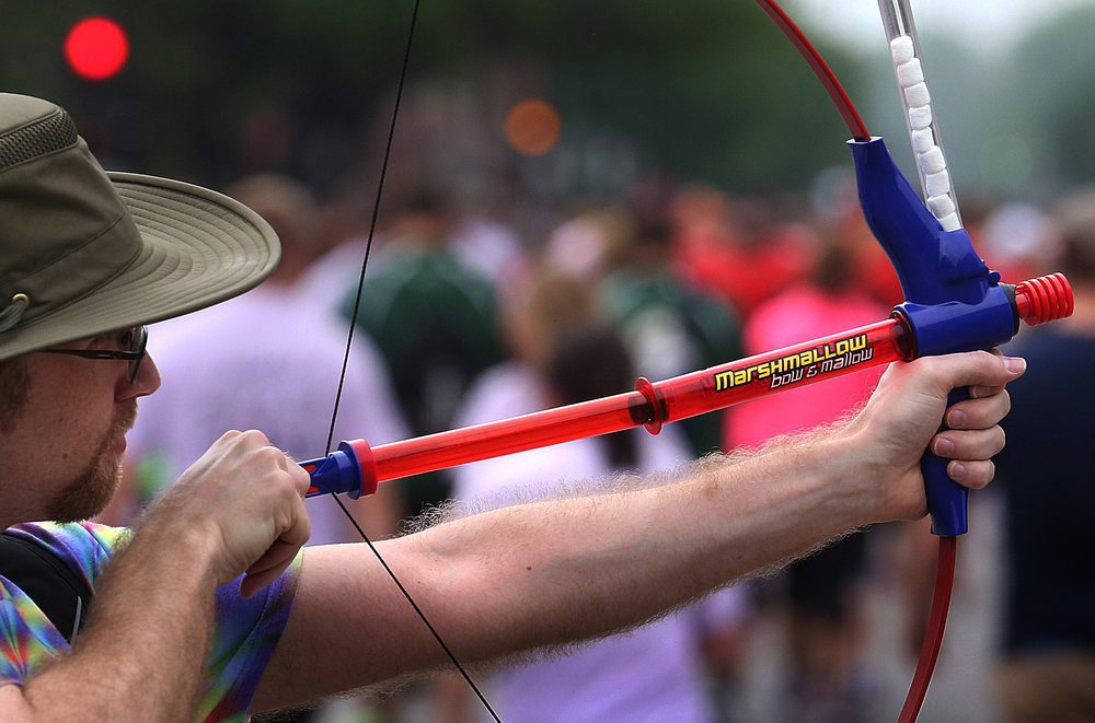 Mike Allen shoots miniature marshmallows from a pneumatic bow and arrow towards runners along Fourth St. David Spencer/The State Journal-Register