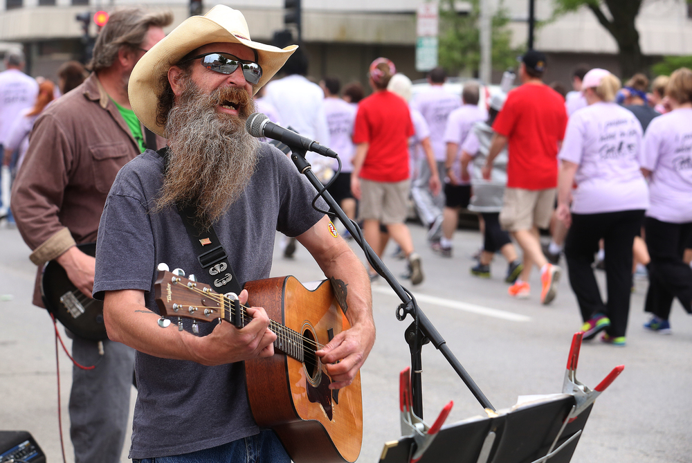 Buckhart-based Wolf Crick Band member Greg Patterson sings along Fourth St. as runners go past Saturday morning. David Spencer/The State Journal-Register