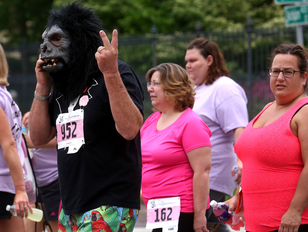 A peaceful gorilla speaks on his cellphone while walking with other race participants along Fourth Street. David Spencer/The State Journal-Register