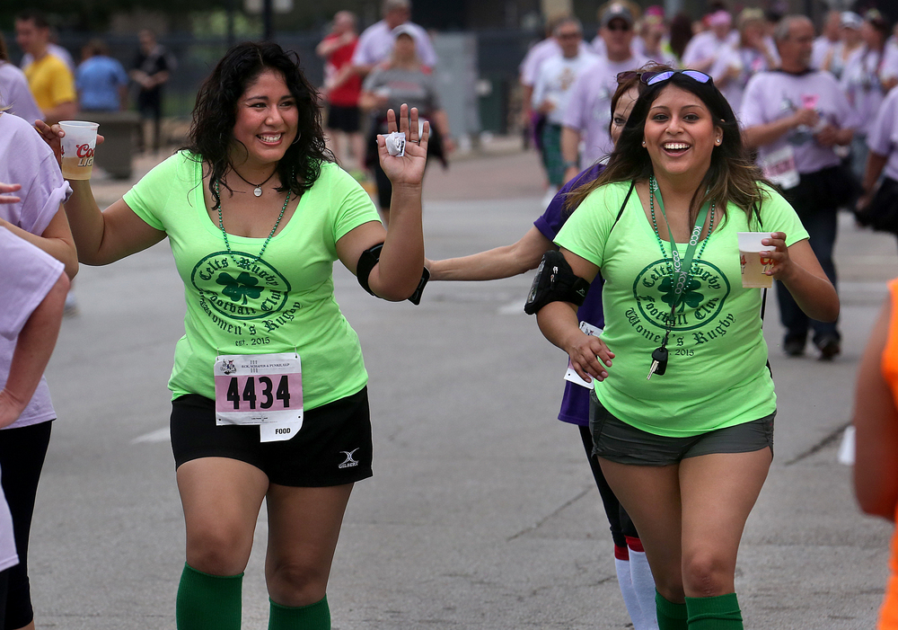 Springfield Celts Womens Rugby Club members Grace Lowe at left and Macy Hamilton did not spill a drop of beer as they cross the finish line together along Washington St. Saturday morning. David Spencer/The State Journal-Register