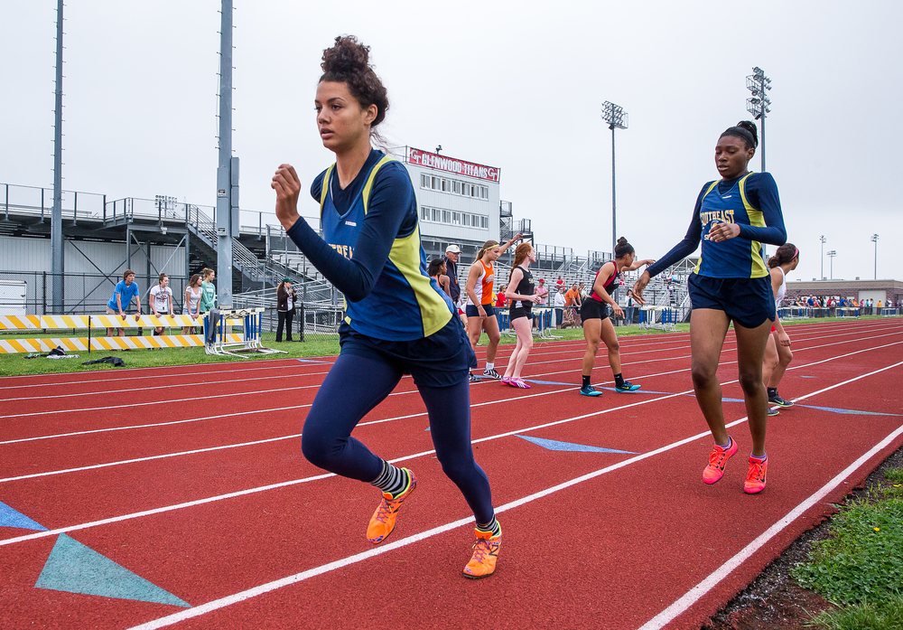 Southeast's Alexis Henry takes the baton from Lisa Crawford to run the final leg of the 4x400m Relay during the Girls Central State Eight Conference Track Meet at Glenwood High School, Saturday, May 9, 2015, in Chatham, Ill. Southeast won the event with a time of 4:01.98. Justin L. Fowler/The State Journal-Register