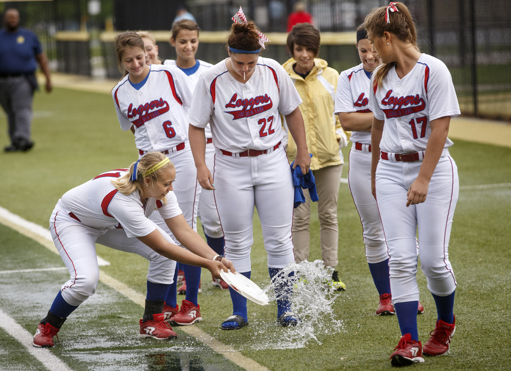 Rachel Wisner scoops water off the field with a bucket lid at Sacred Heart-Griffin as Lincoln Land Community College softball players inspect the field after play was suspeneded due to lighting Friday, May 8, 2015.  Ted Schurter/The State Journal-Register