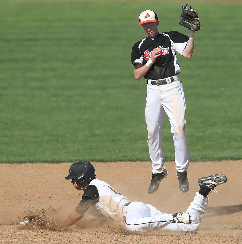 Lanphier second baseman Jake McLean is airborne with the tag as SHG baserunner Cole Daily slides safely in to the bag during first inning action. Daily ended up scoring the Cyclones first run of the game. The Sacred Heart Griffin Cyclones defeated the Lanphier High School Lions 15-5 to win the championship of the City Series Baseball Tournament at Robin Roberts Stadium in Springfield on Tuesday, May 12, 2015. David Spencer/The State Journal-Register